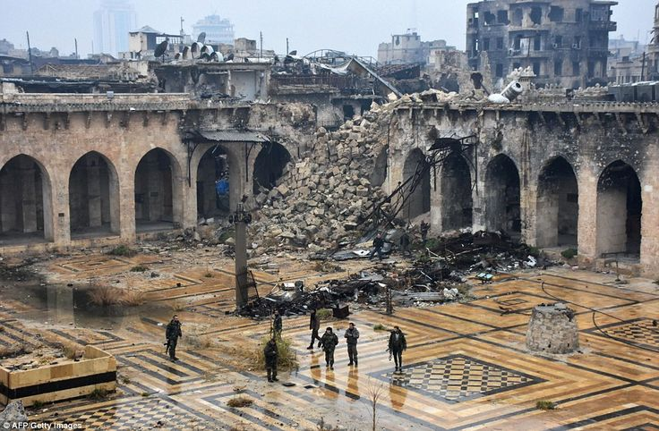 Syrian pro-government forces walking in the ancient Umayyad mosque in the old city of Aleppo, which now lies in ruins