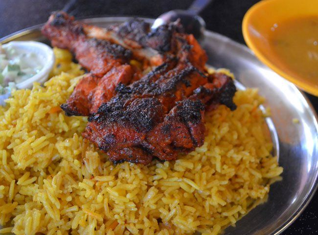 Indian Tandoori Chicken on a bed of Biryani Rice in Georgetown, Penang, Malaysia. Eating in India, Travel in India and Indian Food found throughout India, South Asia, Sri Lanka and Southeast Asia. For more on eating in India check our Blog: http://live-less-ordinary.com/southeast-asia-food/introduction-eating-in-india-indian-food
