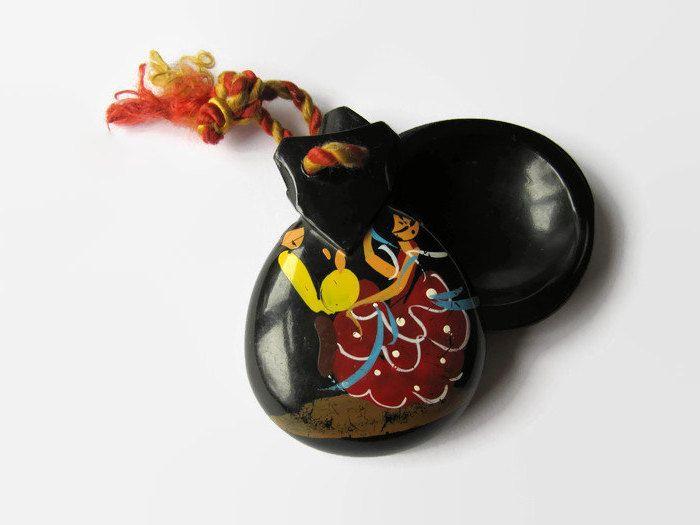 ein Paar schwarze Kastagnetten mit Malerei, ein Schnur aus zwei Fäden - ein in Orange und ein in Gelb, Flamenko-Tänzerin mit rotem Kleid mit weißen Ornamenten, blauem Schal ind gelben Kastagnetten