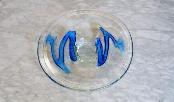 Art glass platter with pedestal base accented with a freeform swirl of cobalt blue made by Kosta Boda, Sweden. Every Kosta Boda piece is a unique work of art, this contemporary platter is in excellent condition.  SIZE: 2in high x 12in diameter