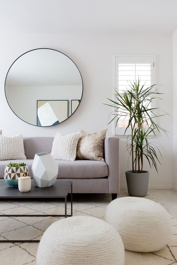Round mirror, grey linen sofa, rope coil ottomans, plant etc. are commonly used in modern geometric living room design. #HomeDecor #LivingSpace