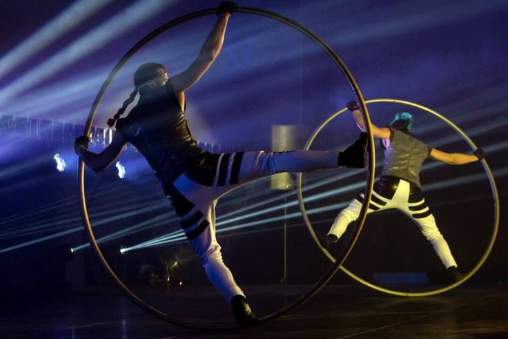 While masterfully controlling his balance, an acrobat rotates on the floor in a Cyr Wheel ring that becomes an extension of his body. The act is full of dyn