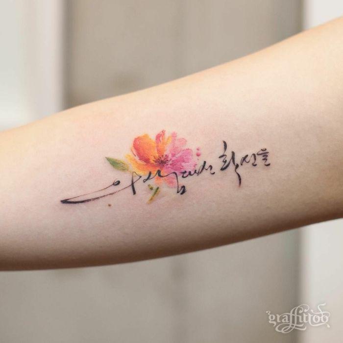 flor de loto tatuaje, tatuaje pequeño en el antebrazo, combinación de flor de acuarela con texto en cursiva negro