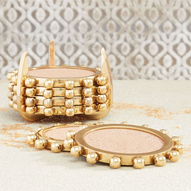 """Julia Buckinghams's Starburst Crown coaster set for Global Views Decor provides a posh punch to a transitional tabletop. These posh essentials feature studded rims in lustrous brass metal, while cork centers offers chic function. The talon-like container offers a final hint of modernism. 5"""" Diameter x 3.5""""H. Metal, cork."""