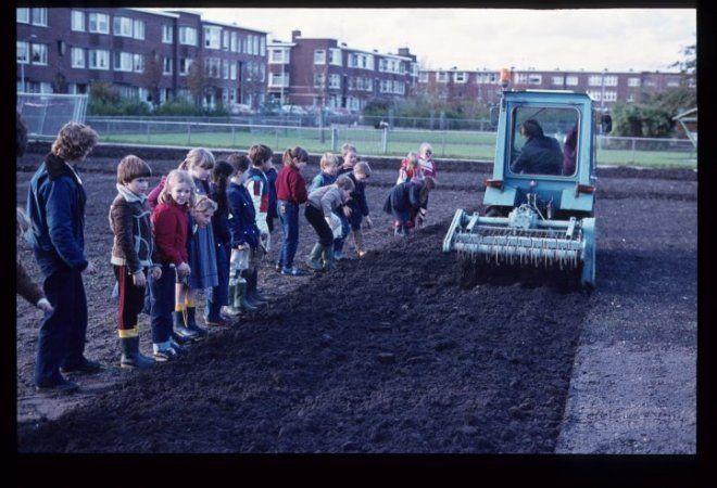 Mient, schooltuinen. De grond wordt machinaal gefreesd tijdens een les. Op de achtergrond de Kornoeljestraat. - 1982
