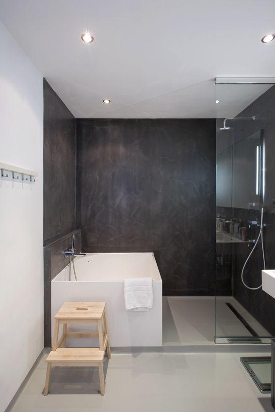 baignoire et douche derrière une paroi + mur en beton ciré noir