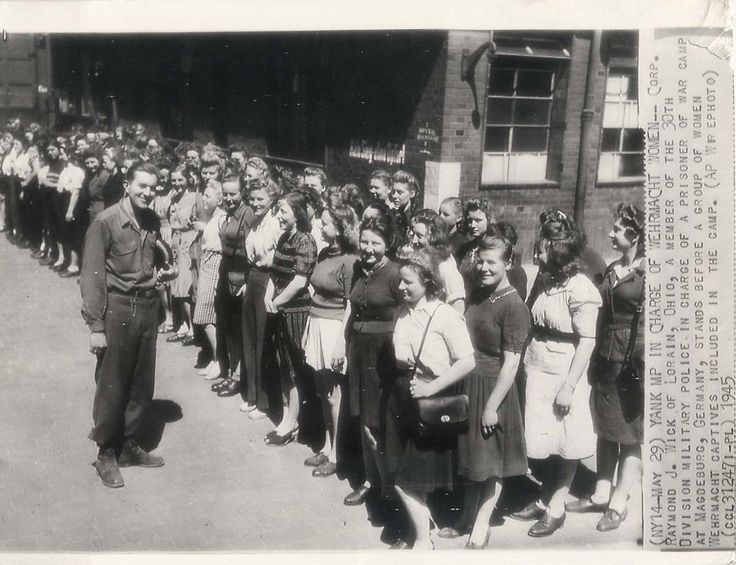 1945- Corp. Raymond Wick, member of the U.S. 30th Division Military Police, in charge of a prisoner of war camp at Magdeburg, Germany, stands before a group of women Wehrmacht captives.