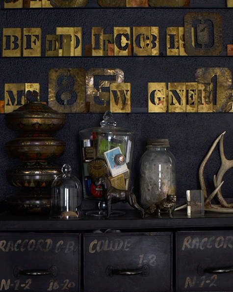 Vintage brass stencils become art against a dark wall.
