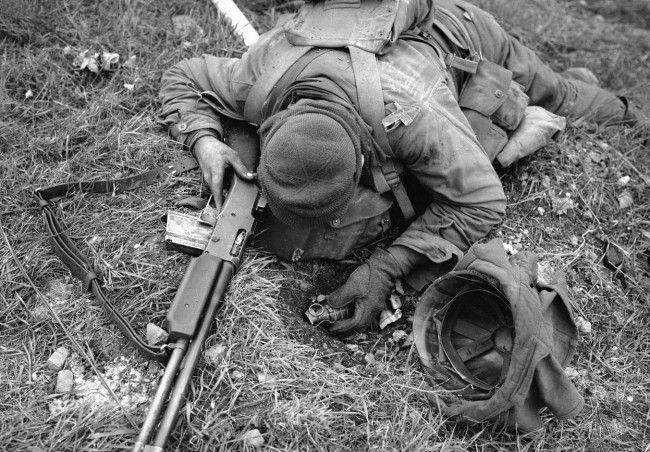 An unidentified American soldier, shot dead by a German sniper, clutches his rifle and hand grenade in March of 1945 in Coblenz, Germany. (AP Photo/Byron H. Rollins)