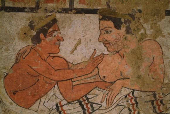 An Etruscan transgender marriage, from the Tomb of the Infernal Chariot. Two men are dining on a couch at a banquet, looking at each other and touching each other as lovers. In Etruscan art men are painted red, from their days in the sun. Women are painted white. Of the two men on the couch, one is painted red and the other is painted white, with the stubble of a beard, so that there will be no doubt about his sex. He/she plays the role of the wife, spending her days in the home out of the…