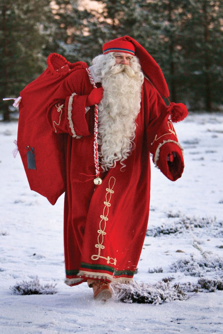 Photo by Bob Strong. Santa Claus dressed in a traditional Finnish costume, totes a bag of toys in Rovaniemi, Finland
