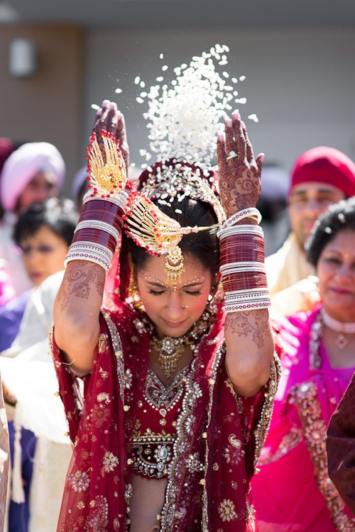 According to the Hindu tradition, as the bride steps out of the house, she throws back handfuls of rice over her head. This signifies that the bride is paying back or returning whatever her parents gave her in all the years she stayed with them; and wishes for prosperity to always flourish in the house she is leaving behind. #bride #indianbride #weddingtradition #tradition