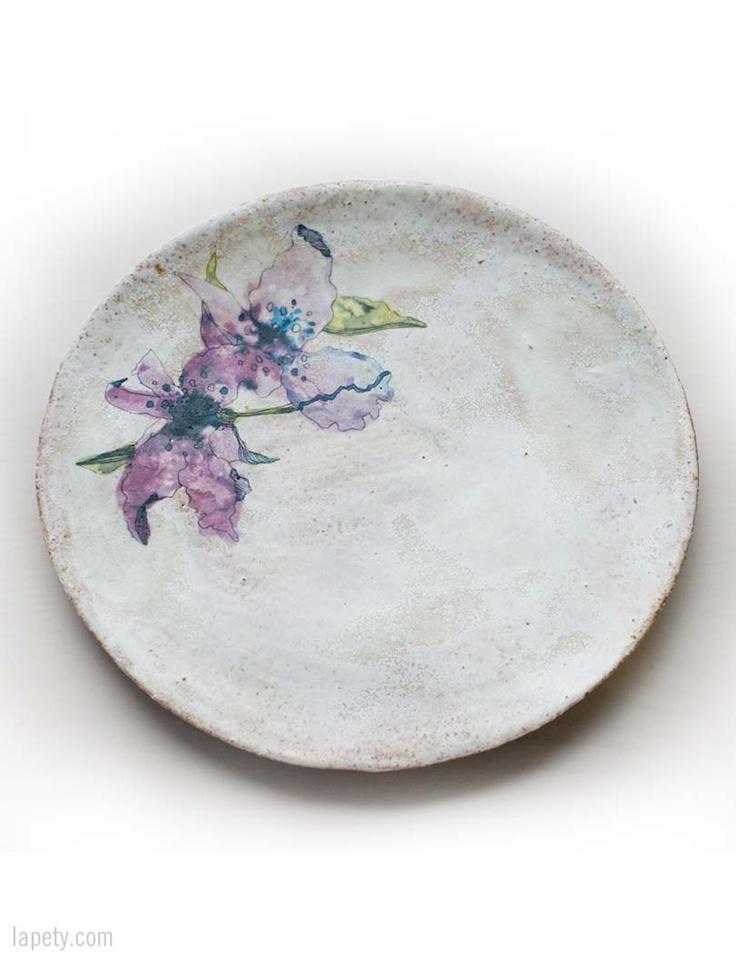 Plato en gres esmaltado, modelado y decorado a mano con temas inspirados en la botánica amazónica. Es perfecto para decorar la mesa o los rincones de tu hogar. Se puede utilizar para alimentos y lavar en lavavajillas. Medidas: 28x2cm