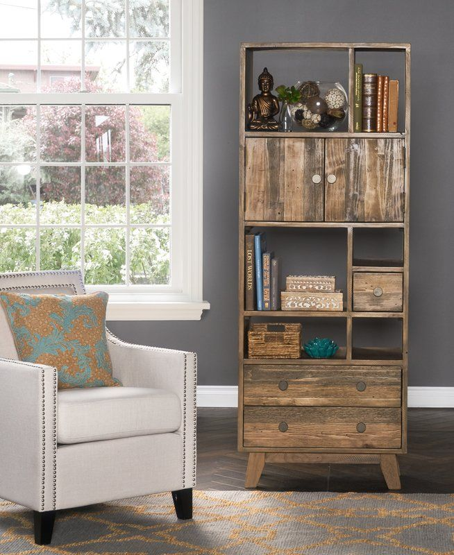 The Brayden Studio Samuel standard bookcase is a versatile storage solution made from solid, reclaimed pine. This vertical and sustainably sourced unit features a cabinet, three drawers of various sizes, and multiple shelves. Iron knobs with a brass finish complete the look and add to the unit's rustic charm. No matter your space or storage requirements, the Samuel standard bookcase will meet your needs and elevate your décor.