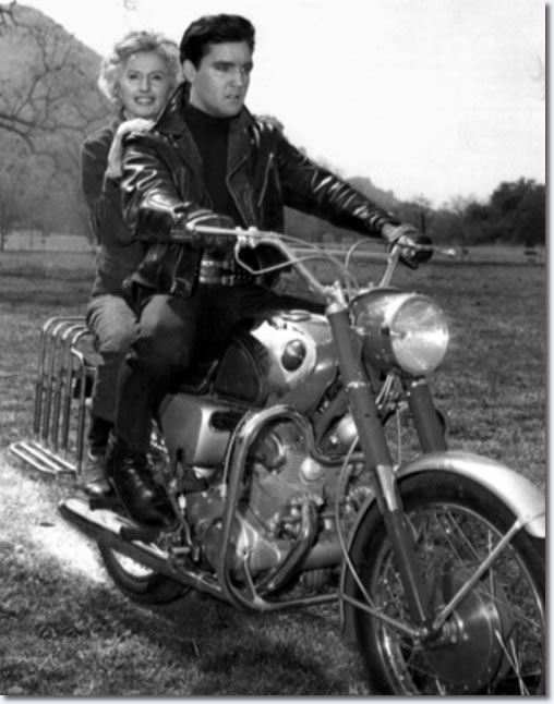 When Elvis Presley, who rides a motorcycle in current film, 'Roustabout', learned co-star Barbara Stanwyck could ride a motorcycle, Elvis promptly hoisted the four-time Academy Award nominee aboard a motorcycle built for two and they were off in a cloud of dust to the amazement of everybody March 20, 1964, in Thousand Oaks, Calif. Elvis and Miss Stanwyck are shown in a cow pasture where the film company was on location.