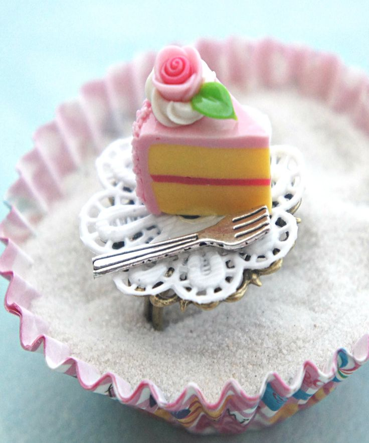 This ring features a slice of handmade strawberry cake sculpted from polymer clay. It sits on a white paper doily along with a miniature fork. The paper doily is attached to an adjustable bronze filig