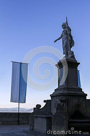 Warrior of marble called Statua della Liberta and Civil flagin. San Marino.