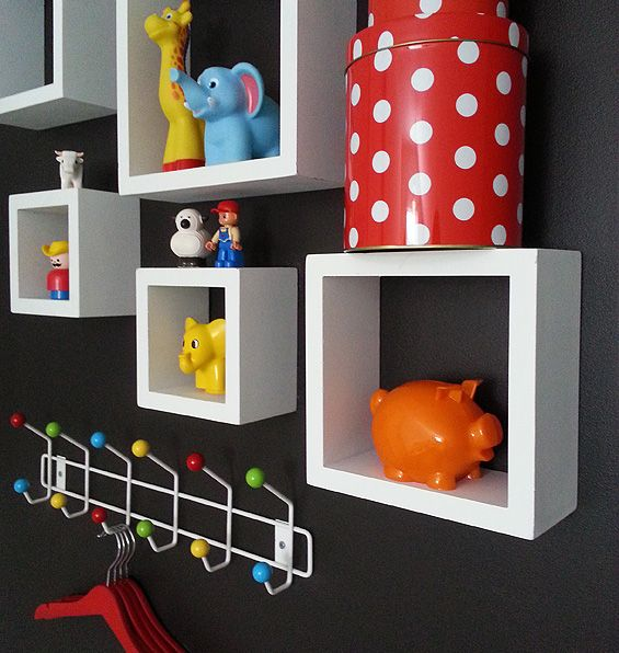 White cube shelves against a wall painted black with lots of bright colored toys in kids room. #kidsroom #duplo #cubeshelves