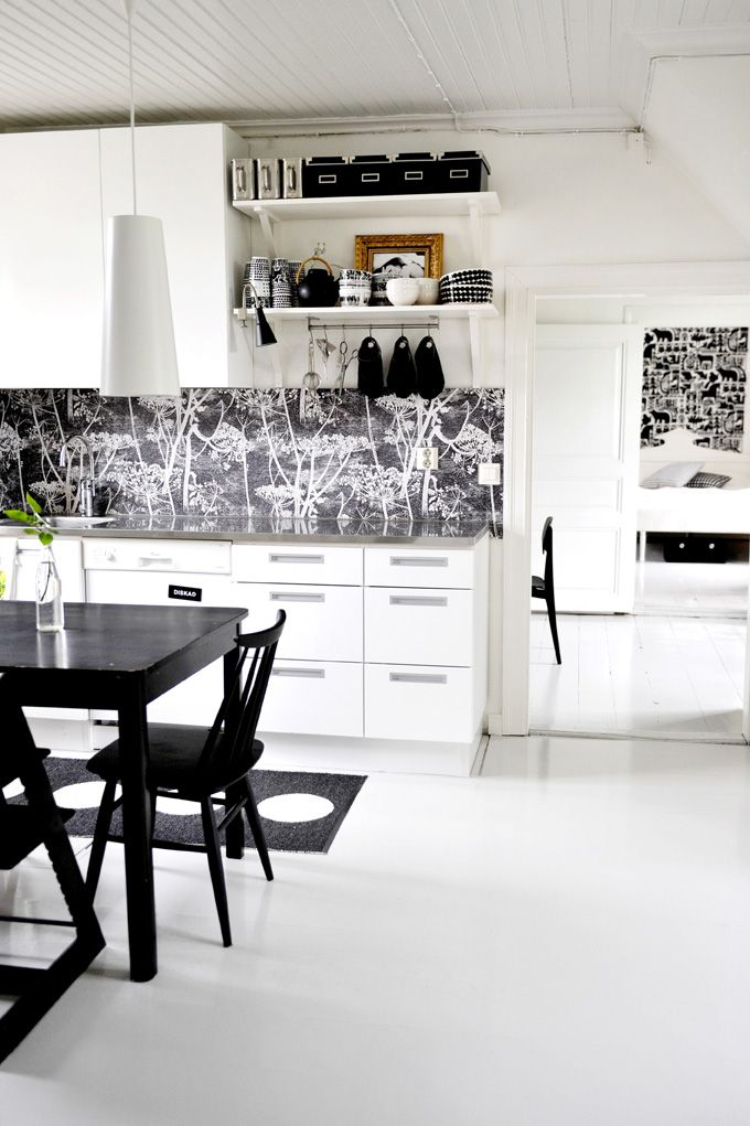 Love the wallpapered splashback in this black & white kitchen. Cole & Son Cow Parsley wallpaper.