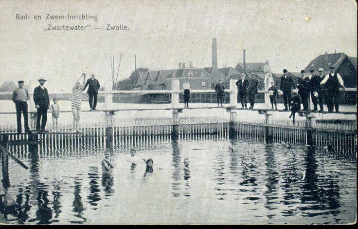 """Katerdijk, zwembad in het Zwartewater van BZZ (Bad- en Zweminrichting Zwartewater, sinds 1990 Swoll 1894), ca. 1920. Rond 1900 waren er twee """"zwembaden"""" in Zwolle, een in het Zwartewater aan de Katerdijk, de ander (het Weteringbad) in het Almelose Kanaal bij de Menistenstraat. Het waren afgezette delen van het water, met krakende vlonders en eenvoudige badhokjes. In de jaren dertig kwam hieraan een eind. Het Stilobad sportfondsenbad aan de Turfmarkt en het Openluchtbad aan de Ceintu..."""