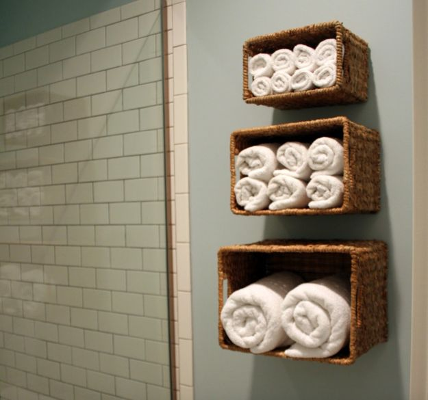 Hang baskets in the bathroom to store towels. | 19 No-Brainer Hacks That'll Make Your Home Really Organized