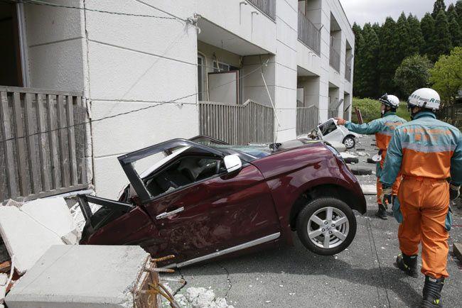 行方不明者を捜索する警察官と建物に押しつぶされた車=熊本県南阿蘇村
