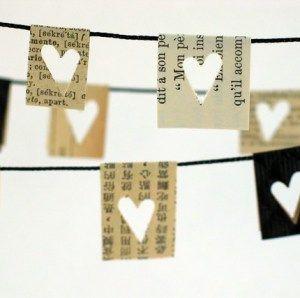 Filigrane Papiergirlande aus bedrucktem Papier. Aus Zeitungspapier oder Bücherseiten werden kleine Rechtecke geschnitten um eine Kordel oder Band verklebt und mit eine Stanze kleine Herzen eingebracht. Einfach schön….