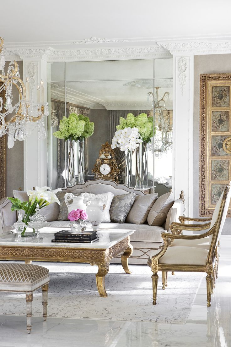Living Room at Maison de Ville: a Parisian pied-a-terre by @ebanistacollect. Featuring our Carpello II Sofa, Palazzo Cocktail Table with a white onyx top, Venetian II Chandelier, Molise Arm Chair, Heraldique II Painting, Vincennes Bench, and an area rug from the Ebanista Rug Collection. Discover more at www.ebanista.com. #FrenchInteriorDesign
