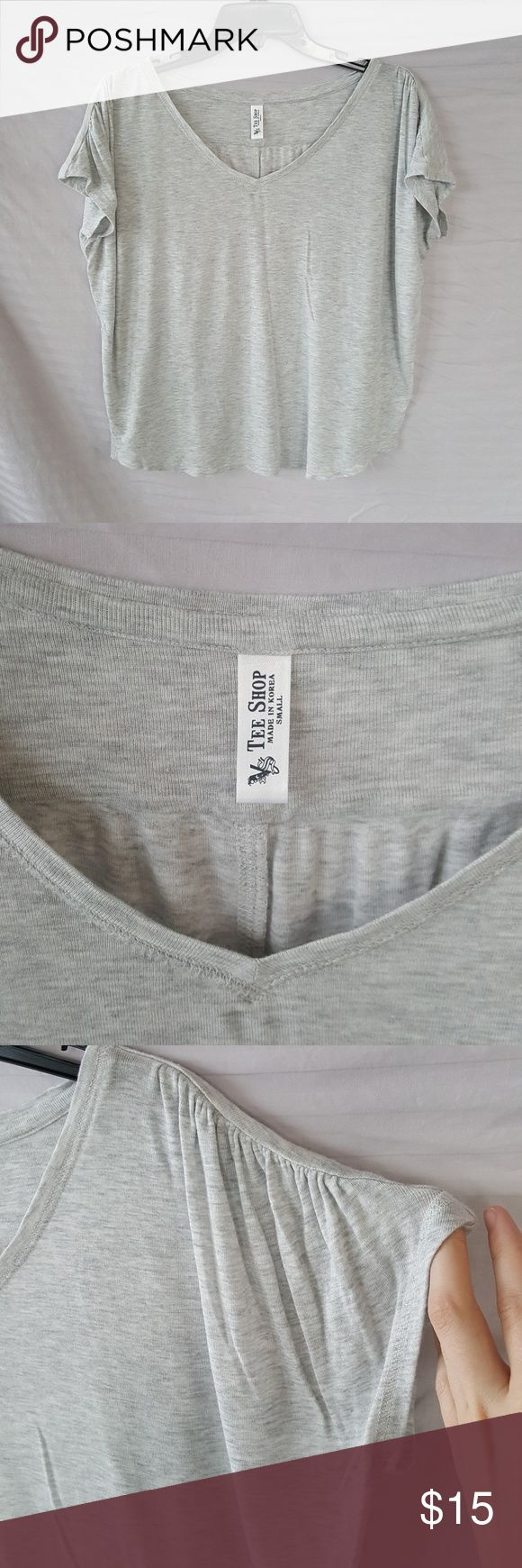 Victoria's Secret Tee Heather Gray Victoria's Secret Tee, Heather Gray, marl, scooping v-neck, curved hem at sides, sleeves have cute ruching, flowy loose fit.  Back of right sleeves has a tiny hole, shown in pics, otherwise in excellent condition.  Bought through Victoria's Secret website, tag says Tee Shop. Victoria's Secret Tops Tees - Short Sleeve