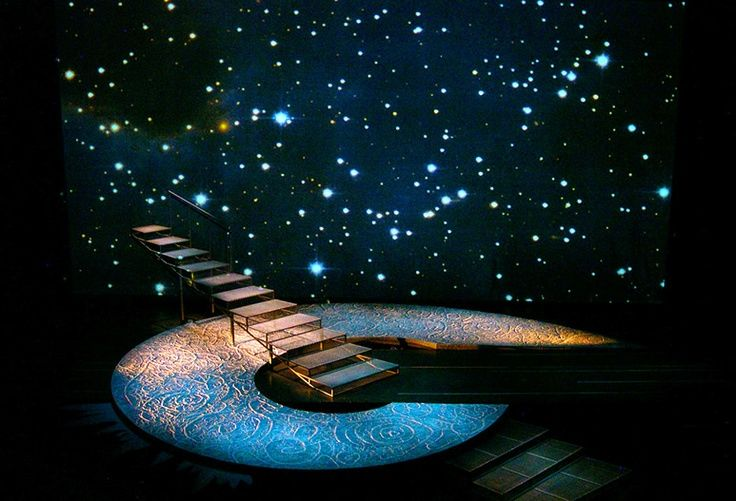 A Wrinkle In Time - set design by Misha Katchman. This scenic design is about color. The orange and blues with the spots of white make it feel galactic and like you're in outer space. The blue and orange are complementary colors so they work well together and make each other stand out. There is a little bit of texture as well. There are swirls and engraving on the spiral object so it is very texturized.