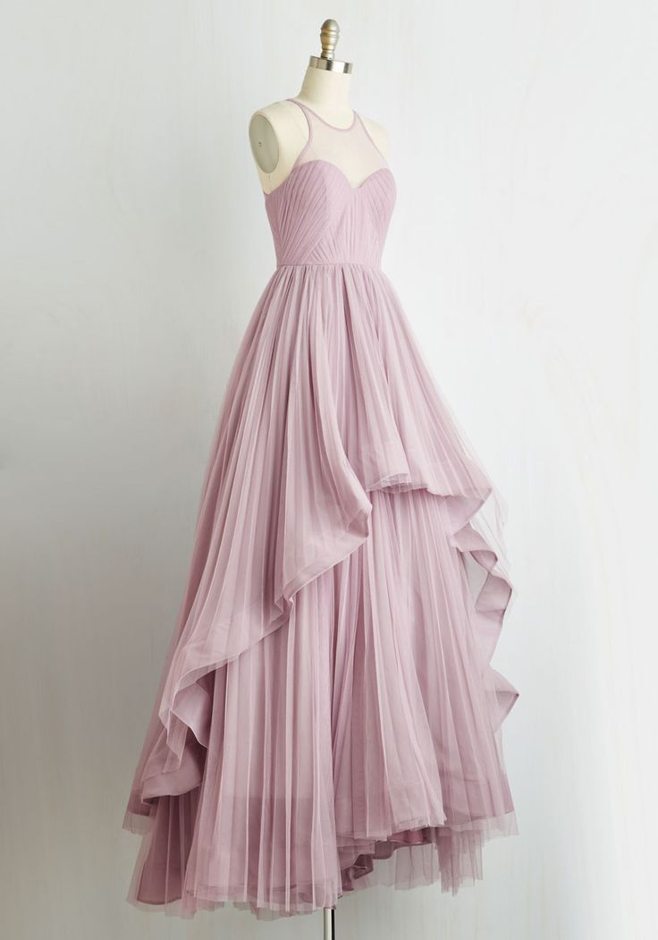 Of all the marvelous ensembles at the ball, yours in this dramatic lilac gown reigns over them all! Sitting atop a voguely voluminous skirt whose netted layers offer a high-low look and full-length flair at once, a pintucked bodice with a tapered illusion neckline exudes unmatched elegance. Such a stunning sight will be available in November!