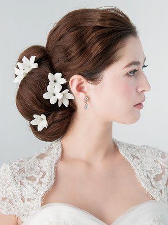 下めに大きくまとめたシニヨンスタイルに白い小花が気品を添えて ウェディングドレス・カラードレスに合う〜シニヨンの花嫁衣装の髪型まとめ一覧〜