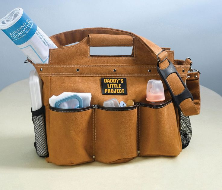 """Designed to look like a work bag Daddy might use, this diaper bag is ornamented with silver rivets and made of faux suede. It measures 17.5"""" x 6"""" x 12.5"""". The bag has a Velcro closure, 7 outside pocke"""