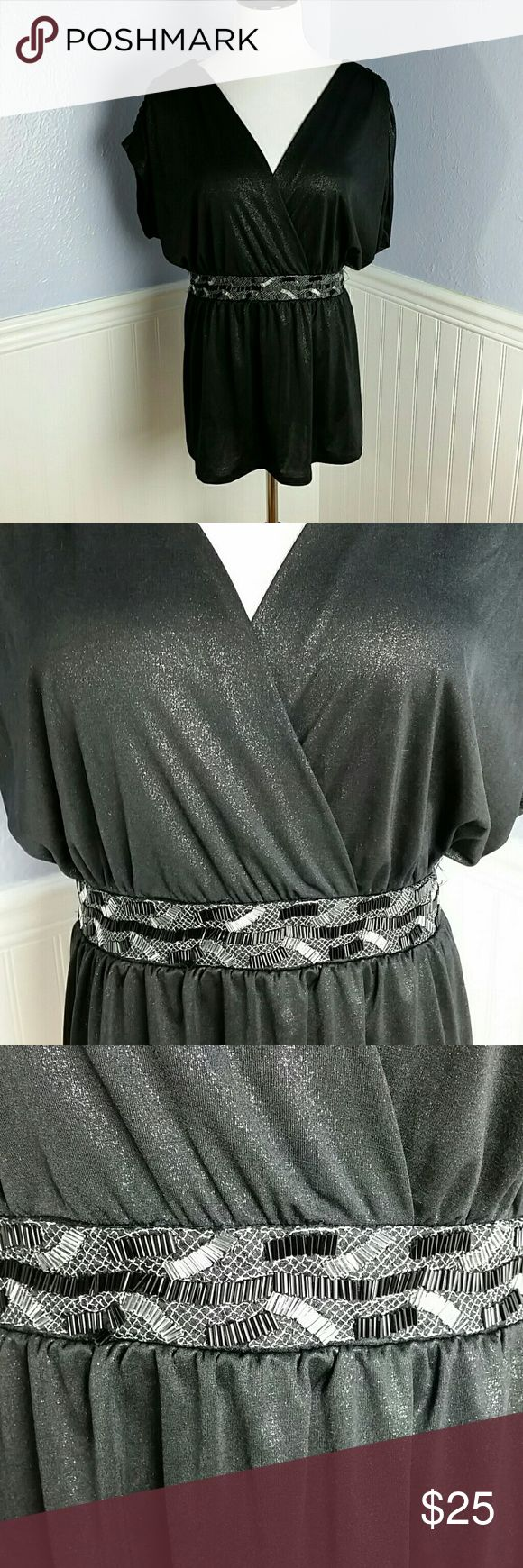 """Torrid Beaded Waist Faux Wrap Top - Torrid Size 0 Perfect top for date night or girls night out  Black silky material with all over silver sparkle.  Beaded Waist band. Faux wrap top, with empire waist and flattering babydoll bottom. Ruched kimono sleeves. Tie back waist. Back features T back style.  94% polyester,  6% spandex.  Length measures 30"""", bust measures 24"""" across,  waist measures 19"""" across.  Some beading missing on waist as shown in photo, one or two missing in other areas, but…"""