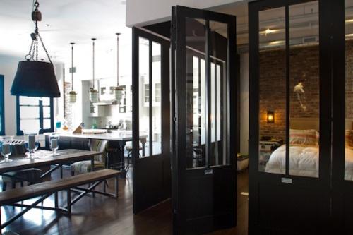 Une chambre entourée d'une verrière esprit atelier.