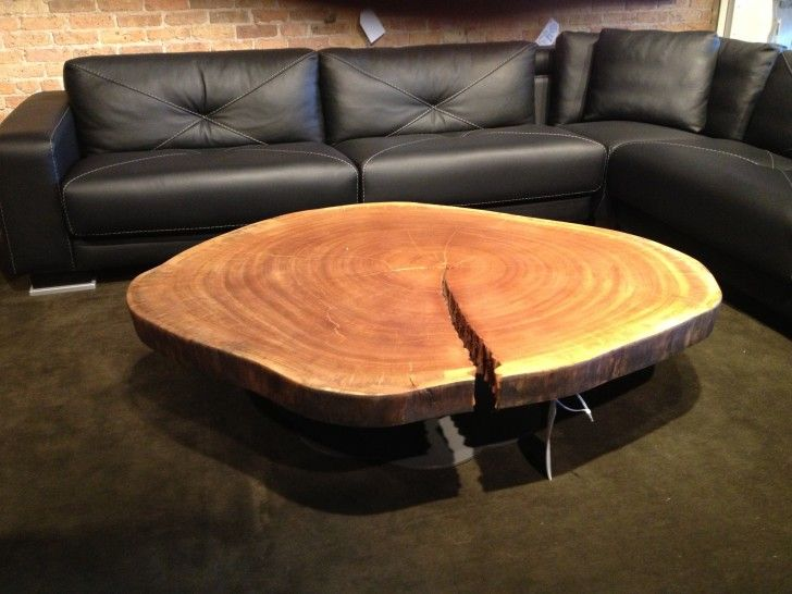 Furniture. round brown floating Tree Stump Coffee Table connected by L  black leather sectional sofa