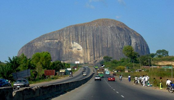 """ZUMA ROCK ::: is a large monolith located in Niger State, Nigeria. It is just north of Nigeria's capital Abuja, along the main road from Abuja to Kaduna, and is sometimes referred to as """"Gateway to Abuja."""" It is depicted on the 100 naira bill. Zuma Rock is 725 meters above its surroundings."""