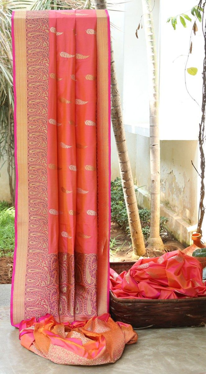 GLOWING PINK IRIDESCENT ORANGE IS INTRICATELY WOVEN IN GOLD AND SILVER ALL OVER. THE COMPLIMENTING PAISLEY BORDER AND PALLU GIVES THE SAREE EXQUISITE FINISH.
