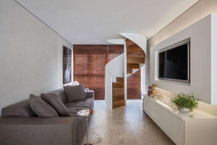 Com a integração da varanda, a área social ficou maior e permitiu criar um espaço de TV. A escada em espiral leva até o escritório.