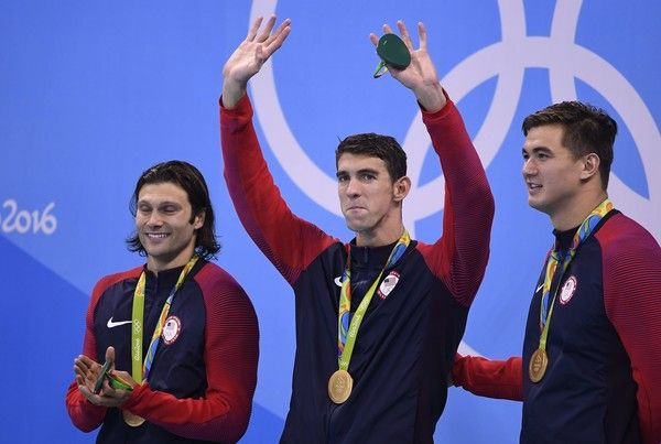 USA's gold medallist team Ryan Murphy (not seen), Cody Miller (L), Michael Phelps (C), Nathan Adrian during the podium ceremony of the Men's swimming 4 x 100m Medley Relay Final at the Rio 2016 Olympic Games at the Olympic Aquatics Stadium in Rio de Janeiro on August 13, 2016.   / AFP / GABRIEL BOUYS