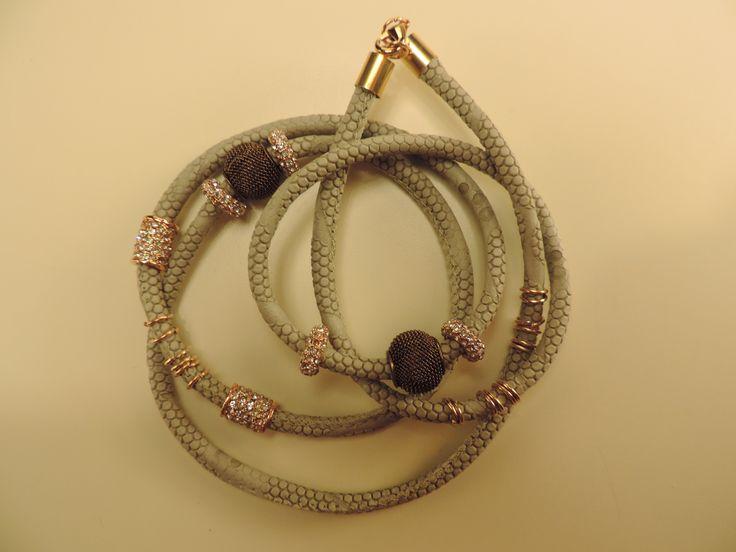 Bracciale a 5 giri di polso, effetto pitonato-caucciù, colore beige, charms corlor oro rosa e bronzo, chiusura dorata con moschettone.