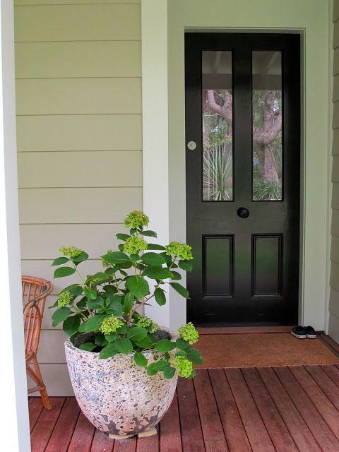 Black front door, weatherboard house.