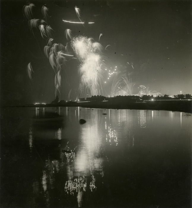 From 1923, High Out Over Lake Ontario, the Glow of Their Flashing Lights and Myriad Colors Reflected in the / Placid Waters, Soar the Rockets That Spring Like Brilliant Flowers From the Great Fireworks Display / Which Nightly Enthralls the Thousands Crowding the Grand Stand at the Canadian National Exhibition.