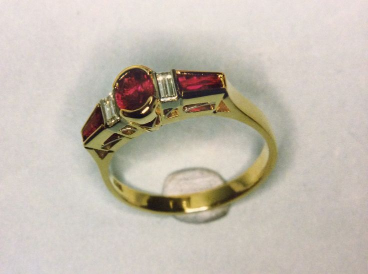 Oval  and tappered Baguette Ruby's alternating with baguette diamonds featuring fine gallery work to the side of the ring and supported by a flow  up band