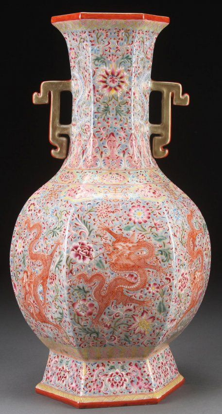 """A CHINESE FAMILLE ROSE PORCELAIN """"DRAGONS"""" VASE. Of hexagonal baluster form with stylized flange handles, each panel decorated with an iron red dragon. Base with Qianlong Nian Zhi mark. Height 17.25 inches."""