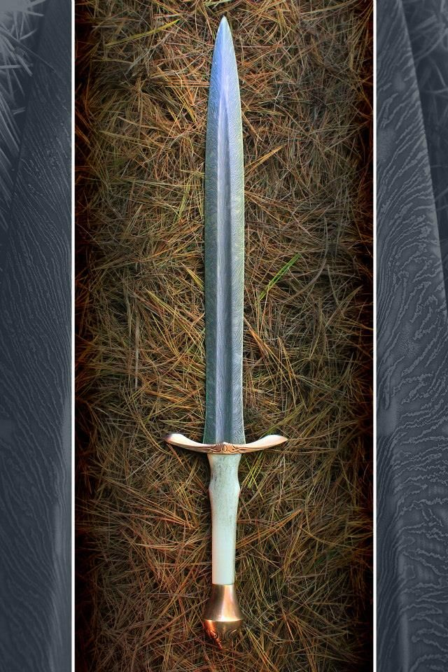"""Bregol Valon (literally meaning """"Fierce Angelic-Guardian"""" in Tolkien's Elvish Quenya language) was crafted and creatively-conceived to life by David DelaGardelle, swordsmith of Cedarlore Forge. The blade was shaped by David from a billet of beautiful """"feathered"""" damascus steel, made by the incredibly talented father and son team at HHH Knives. The sword was crafted by David to be swift, balanced to near weightlessness, agile, and to be violently fierce in the grip of its wielder."""