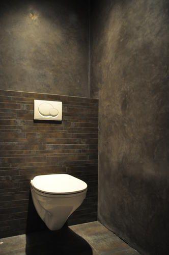 De wanden van deze toilet zijn eerst vlakgezet met een cementgebonden mortel. Daarna afgewerkt met Tadelakt in de kleur Gomera grijs. Het inbouwreservoir is afgewerkt met een mozaiktegel in de kleur antraciet.