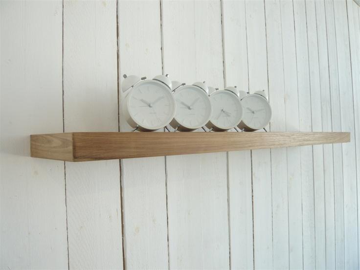 om toch wat hout terug te laten komen, zou ik boven de bank zo'n houten plank hangen, met daarop verschillende fotolijsten met mooie zwart wit foto's...