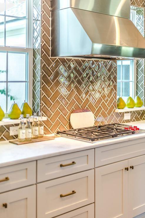 Gray and white kitchen clad in gray herringbone backsplash