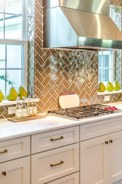 Gray and white kitchen clad in gray herringbone backsplash tiles boasts a stainless steel hood fixed between windows above a Wolf integrated range mounted to a marble countertop accenting white shaker cabinets adorning bronze pulls.